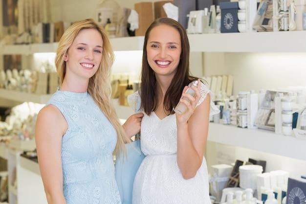 Szczęśliwe kobiety uśmiecha się przy kamerą i trzyma butelkę pachnidło