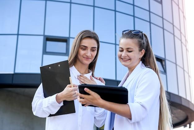 Szczęśliwe kobiety w garniturach z folderu stojącego przed dużym biurem biznesowym