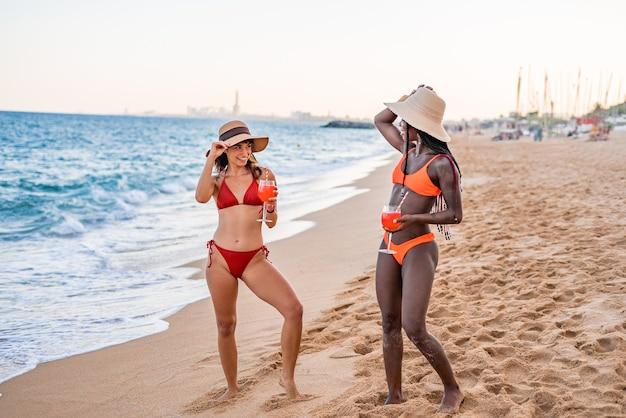 Szczęśliwe kobiety w strojach kąpielowych i czapkach przeciwsłonecznych na plaży
