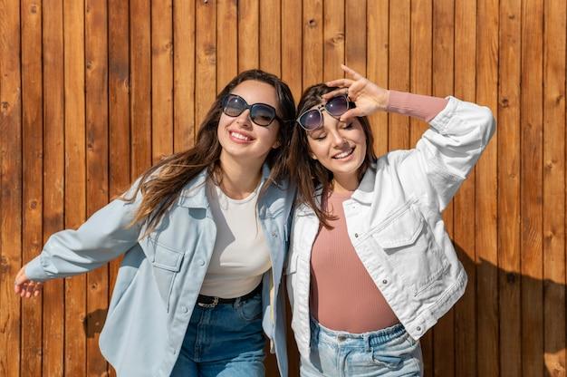 Szczęśliwe kobiety z okularami przeciwsłonecznymi na zewnątrz