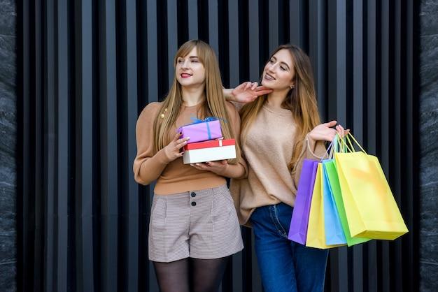 Szczęśliwe kobiety z prezentami i torbami na zakupy chodzą na ulicy miasta. koncepcja obchodów nowego roku i bożego narodzenia