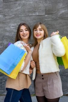 Szczęśliwe kobiety z torbami na zakupy w futrach pozują na ulicy miasta