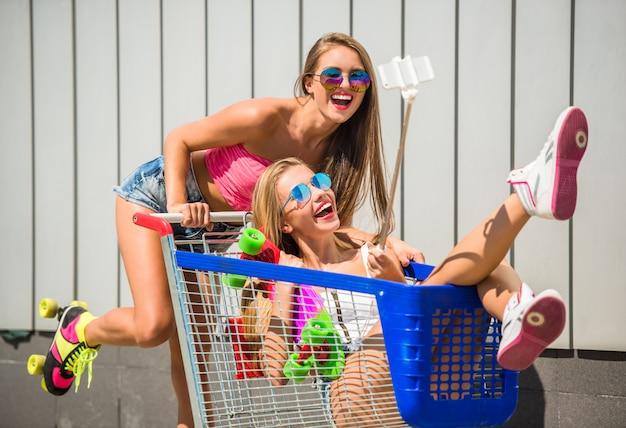 Szczęśliwe koleżanki bawią się i robią selfie.