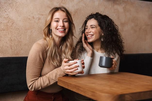 Szczęśliwe koleżanki siedzące w kawiarni rozmawiające ze sobą, pijące herbatę lub kawę