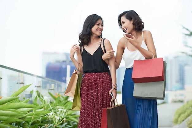 Szczęśliwe koleżanki śmiejące się i żartujące podczas spaceru na świeżym powietrzu po wspólnych zakupach w centrum handlowym