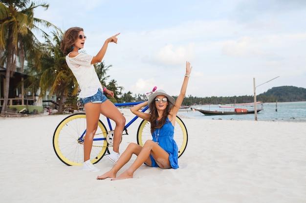 Szczęśliwe koleżanki zabawy na tropikalnej plaży, kobiety podróżujące na wakacje w tajlandii z rowerem