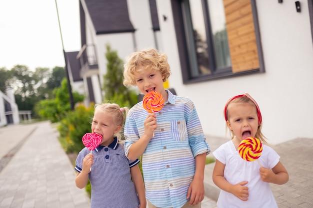 Szczęśliwe ładne dzieci jedzą pyszne słodkie cukierki