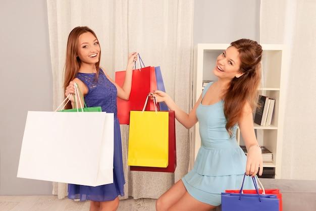 Szczęśliwe ładne siostry pokazujące torby na zakupy z zakupami