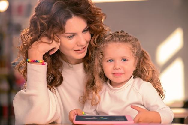 Szczęśliwe macierzyństwo. miła dziewczynka trzymając uśmiech na twarzy, patrząc prosto w kamerę