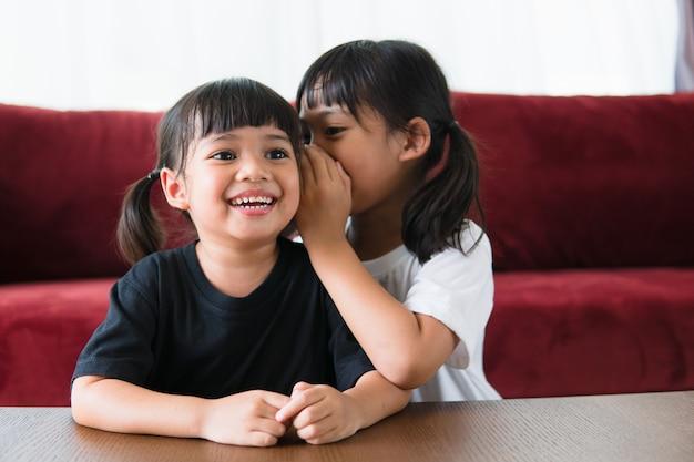 Szczęśliwe małe azjatyckie rodzeństwo dzielące się sekretami