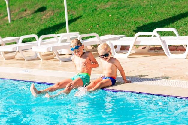 Szczęśliwe małe dzieci bawią się na basenie w ośrodku wypoczynkowym