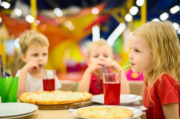 Szczęśliwe małe dzieci jedzą obiad