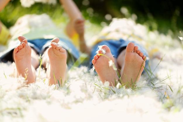 Szczęśliwe małe dzieci, leżące na trawie z piórami, barefo