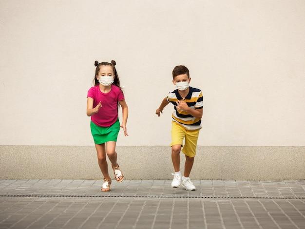 Szczęśliwe małe dzieci noszenie maski ochronnej skakanie i bieganie na ulicy miasta. wygląda szczęśliwie, wesoło, szczerze. miejsce. dzieciństwo, koncepcja pandemii. opieka zdrowotna, pandemia koronawirusa.