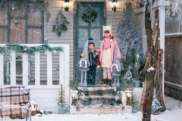 Szczęśliwe małe dzieci siedzą na ganku świątecznego domu, pada śnieg na świeżym powietrzu
