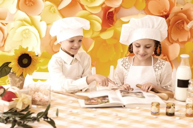 Szczęśliwe małe dzieci w postaci kucharza gotują pyszne