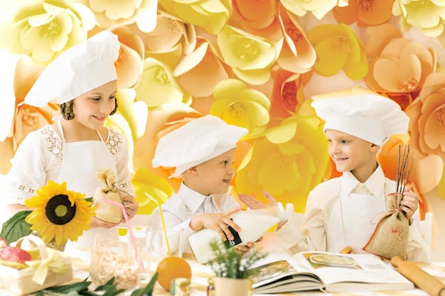 Szczęśliwe małe dzieci w postaci kucharza przygotowują pyszne posiłki