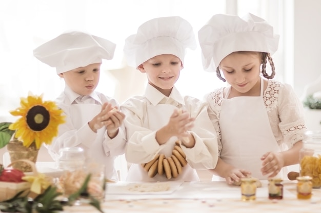 Szczęśliwe małe dzieci w postaci kucharza przygotowującego pyszne dania