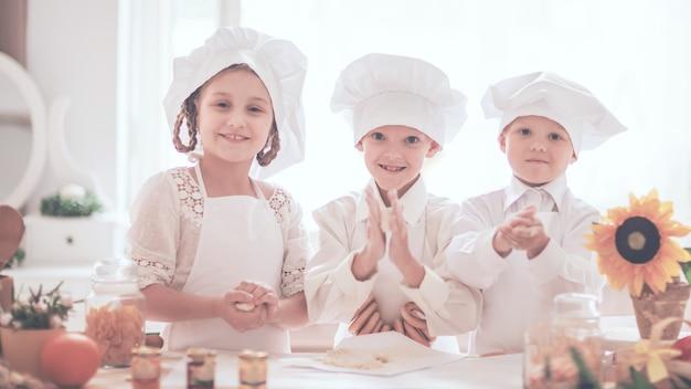 Szczęśliwe małe dzieci w postaci szefa kuchni przygotowują pyszne dania w kuchni