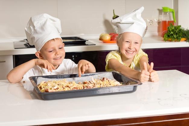 Szczęśliwe małe dzieci z powodzeniem zrobiły pizzę w kuchni