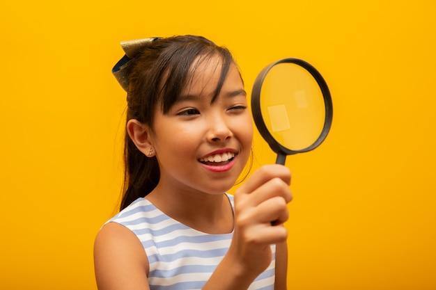 Szczęśliwe małe dziecko azjatyckie z lupą