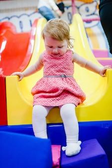 Szczęśliwe małe dziecko, dziewczynka 1-2 lata, dzieci jeżdżące w górę, w dół na zjeżdżalni, bawiące się w suchym basenie, w centrum gier, wesołe miasteczko w pokoju dziecięcym na urodziny. kryty plac zabaw.
