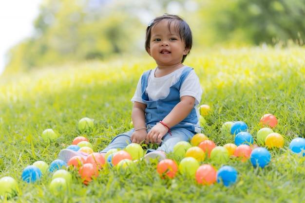Szczęśliwe małe dziecko i kolorowe kulki w parku