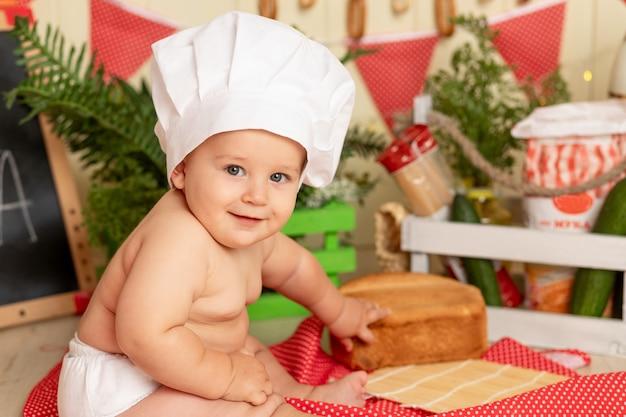 Szczęśliwe małe dziecko w kapeluszu szefa kuchni siedzi w kuchni z chlebem