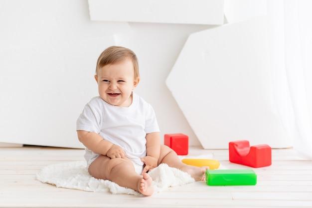 Szczęśliwe małe dziecko w wieku sześciu miesięcy w białej koszulce i pieluchach bawi się w domu na macie w jasnym pokoju z jasnymi kolorowymi kostkami