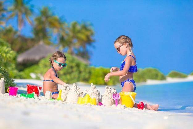 Szczęśliwe małe dziewczynki bawić się z plażowymi zabawkami podczas tropikalnego wakacje