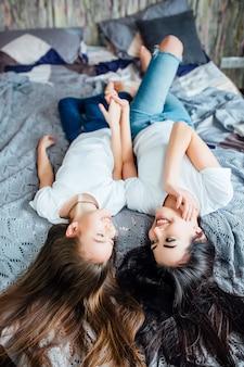 Szczęśliwe małe i starsze dziewczynki leżące na siostrach widok z tyłu