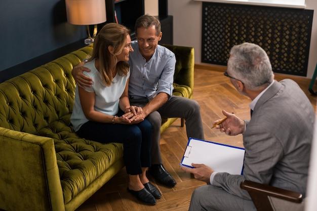 Szczęśliwe małżeństwo w średnim wieku siedzi na kanapie, uśmiechając się i patrząc na siebie podczas sesji terapeutycznej