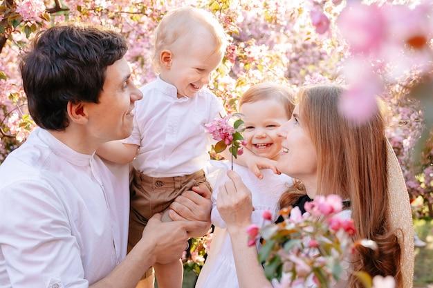 Szczęśliwe małżeństwo z dziećmi z radością patrzy na różowe kwiaty jabłoni w parku