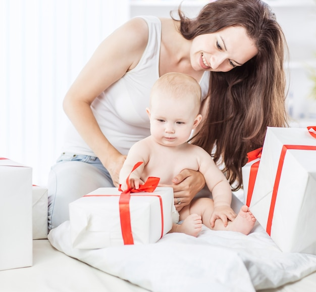 Szczęśliwe matki swojego rocznego dziecka rozważają pudełko z zakupami zakupionymi na święta