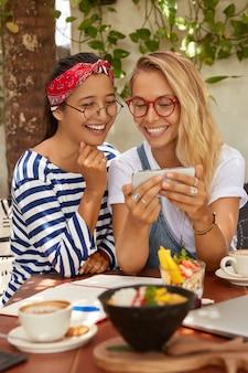 Szczęśliwe międzyrasowe młode dziewczyny śmieją się z zabawnych zdjęć, oglądają na smartfonie, bawią się razem