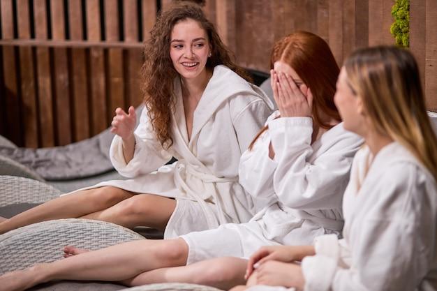Szczęśliwe miłe kobiety bawią się nawzajem śmiejąc się w centrum spa
