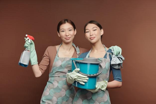 Szczęśliwe młode bliźniaczki w fartuchach i rękawiczkach, trzymając detergent, prochowiec i wiadro, stojąc blisko siebie przed kamerą