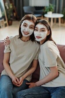 Szczęśliwe młode czułe bliźniaczki z glinianą maską na twarzach siedzących na kanapie przed kamerą, podczas gdy jedna z nich obejmuje swoją siostrę
