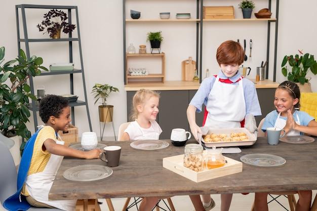 Szczęśliwe młode dzieci z surowymi ciasteczkami na tacy stojącej przy stole w kuchni przed kamerą