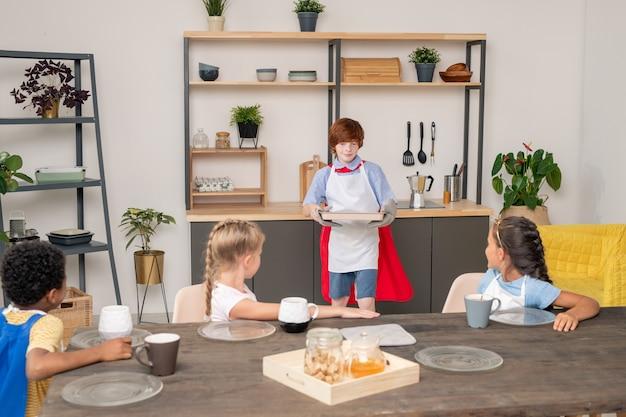 Szczęśliwe młode dzieci z surowymi ciasteczkami na tacy stojącej przy stole w kuchni