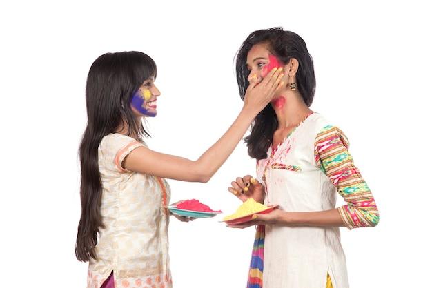 Szczęśliwe młode dziewczyny bawią się kolorowym proszkiem na festiwalu kolorów holi