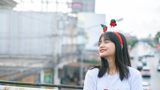 Szczęśliwe młode dziewczyny noszą świąteczny kapelusz na tle widoku miasta.