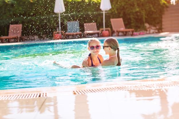 Szczęśliwe młode dziewczyny w okularach przeciwsłonecznych bawią się na basenie
