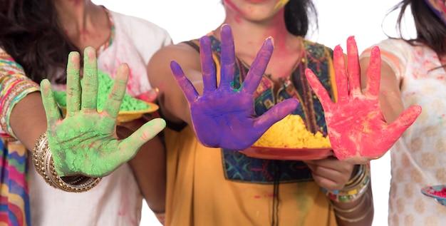 Szczęśliwe młode dziewczyny zabawy z kolorowym proszkiem na festiwalu kolorów holi