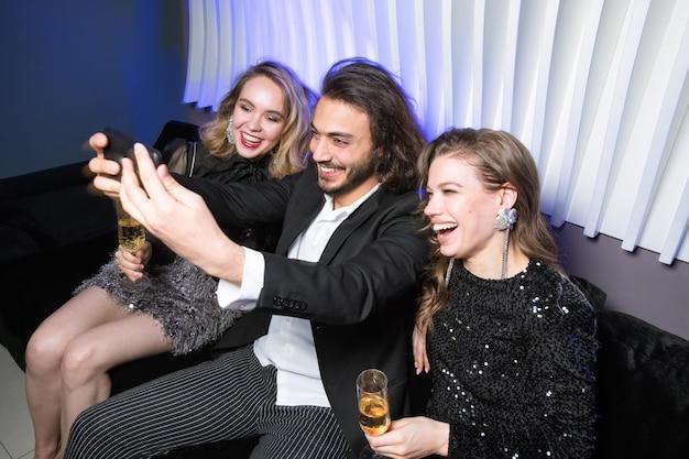 Szczęśliwe młode efektowne kobiety z szampanem i eleganckim mężczyzną z smartphone co selfie na kanapie w klubie nocnym