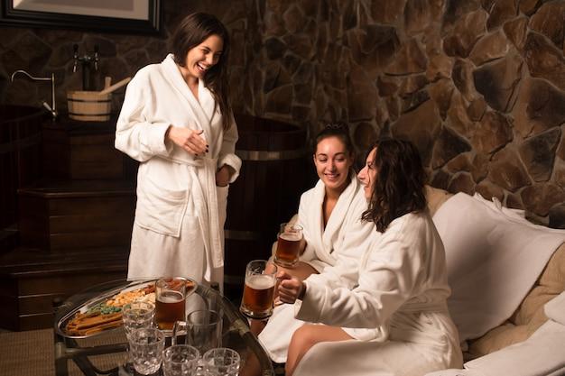 Szczęśliwe młode kaukaskie kobiety w szlafroku siedzą przy basenie w saunie, popijając zimne piwo.