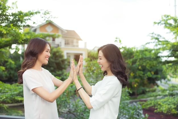 Szczęśliwe młode kobiety, dobrze ubrane przyjaciółki, uśmiechnięte, stojące razem