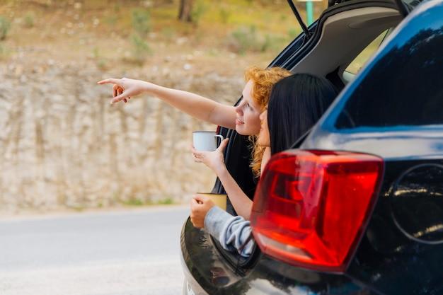 Szczęśliwe młode kobiety relaksuje w maszynowym bagażniku