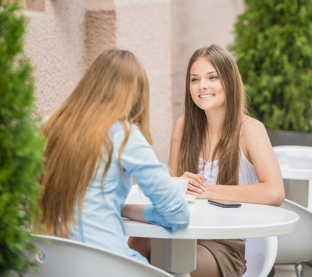 Szczęśliwe młode kobiety siedzi przy miastową kawiarnią.