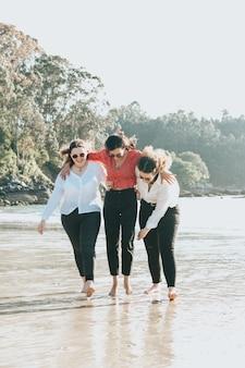 Szczęśliwe młode kobiety śmiejące się i uśmiechające się na plaży w letni dzień, cieszące się wakacjami, koncepcja przyjaźni na świeżym powietrzu the